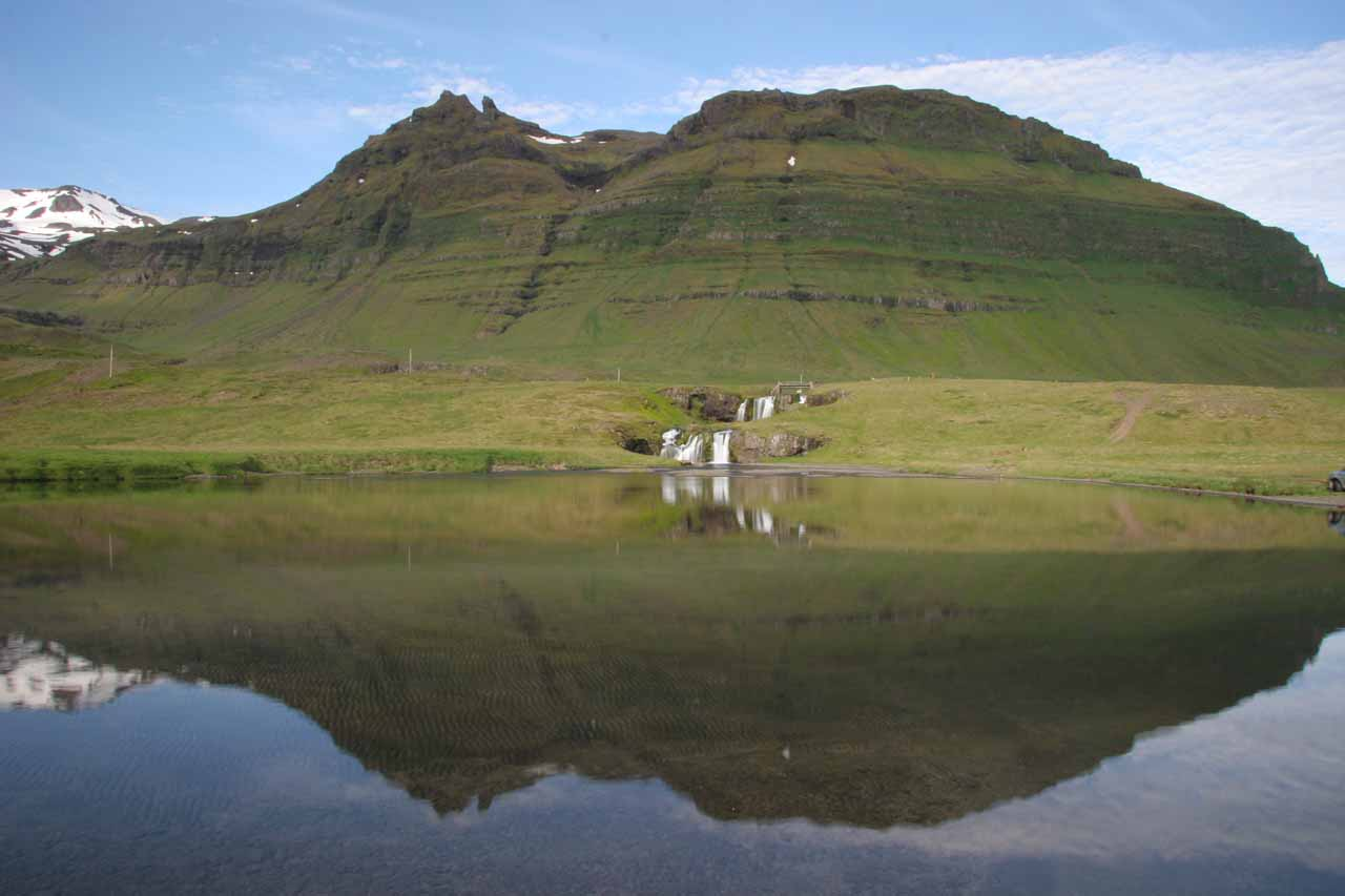 Contextual look towards Kirkjufellsfoss from across a calm inlet providing gorgeous reflections of both the falls and mountain behind it