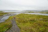 Kirkjufellsfoss_061_08172021 - Looking down at the context of the trail by Kirkjufellsfoss with Grundarfjordur in the distance under low clouds