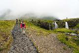 Kirkjufellsfoss_093_08172021 - Julie on the trail alongside the upper drop of Kirkjufellsfoss with lots of people around the falls trying to recreate that Instagram shot