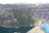 Kjerag_371_06222019 - Another person lying on her belly to look over the sheer 1000m dropoffs into Lysefjorden at Nesatindane