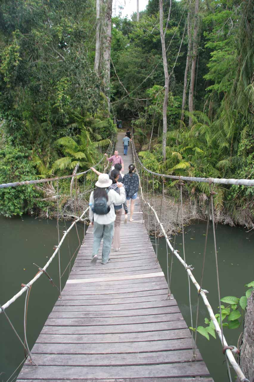Julie on a swinging bridge following other tourists towards a signposted waterfall