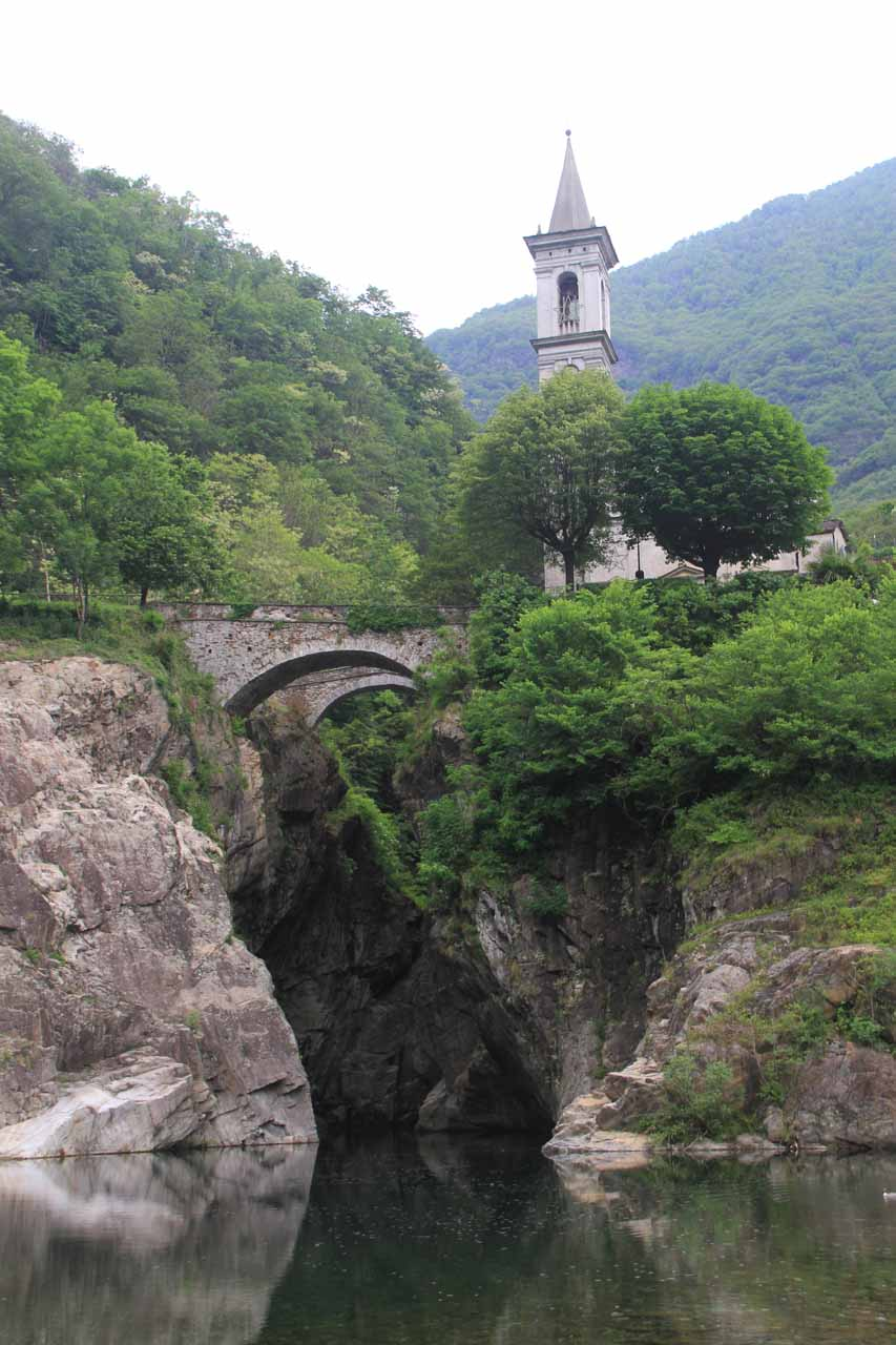 Looking directly at the historic church, the medieval bridge, and the gorge below from the banks of the river at L'Orrido di Sant'Anna