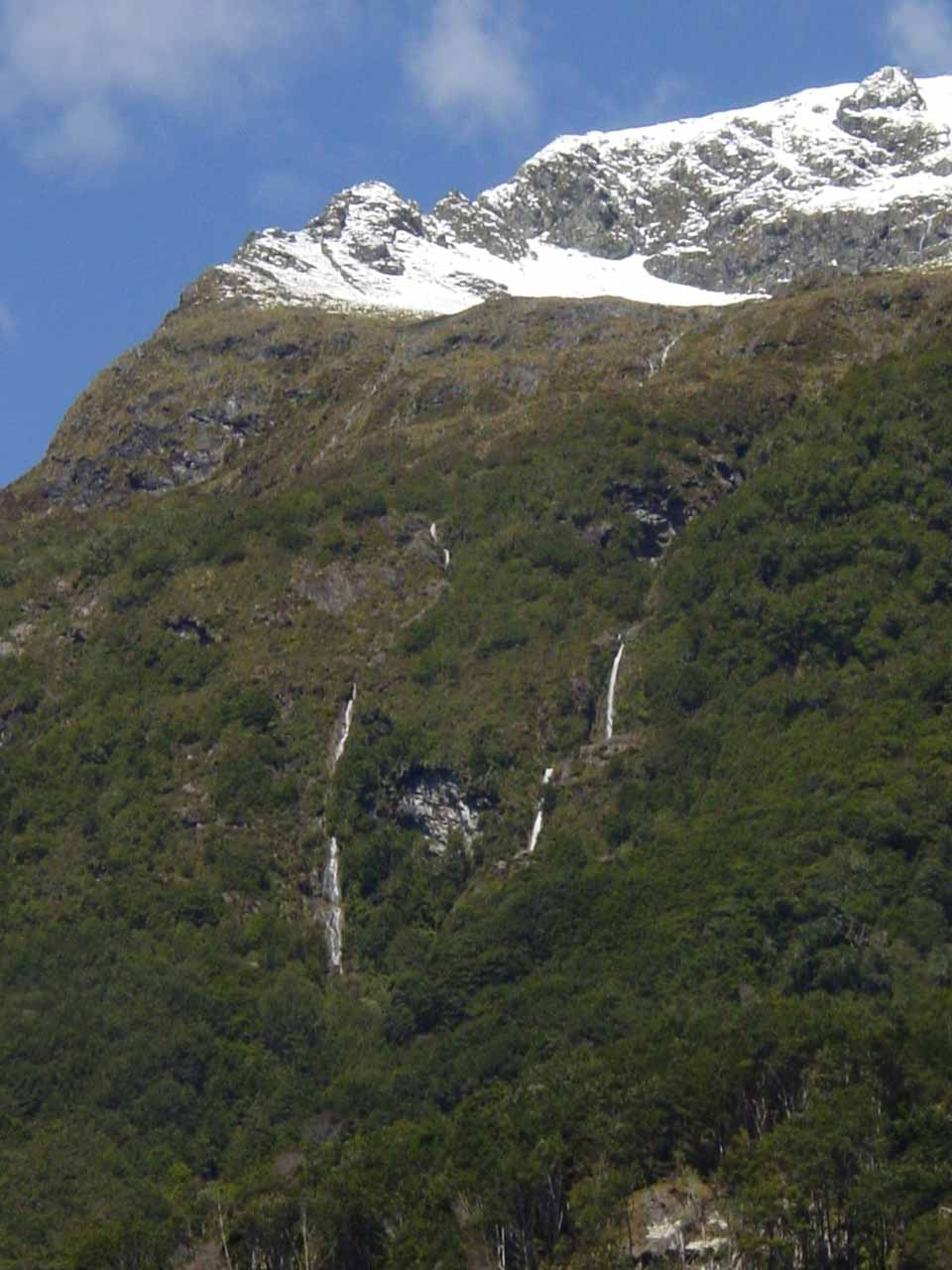 Looking up towards a pair of ephemeral waterfalls under some snowy mountains