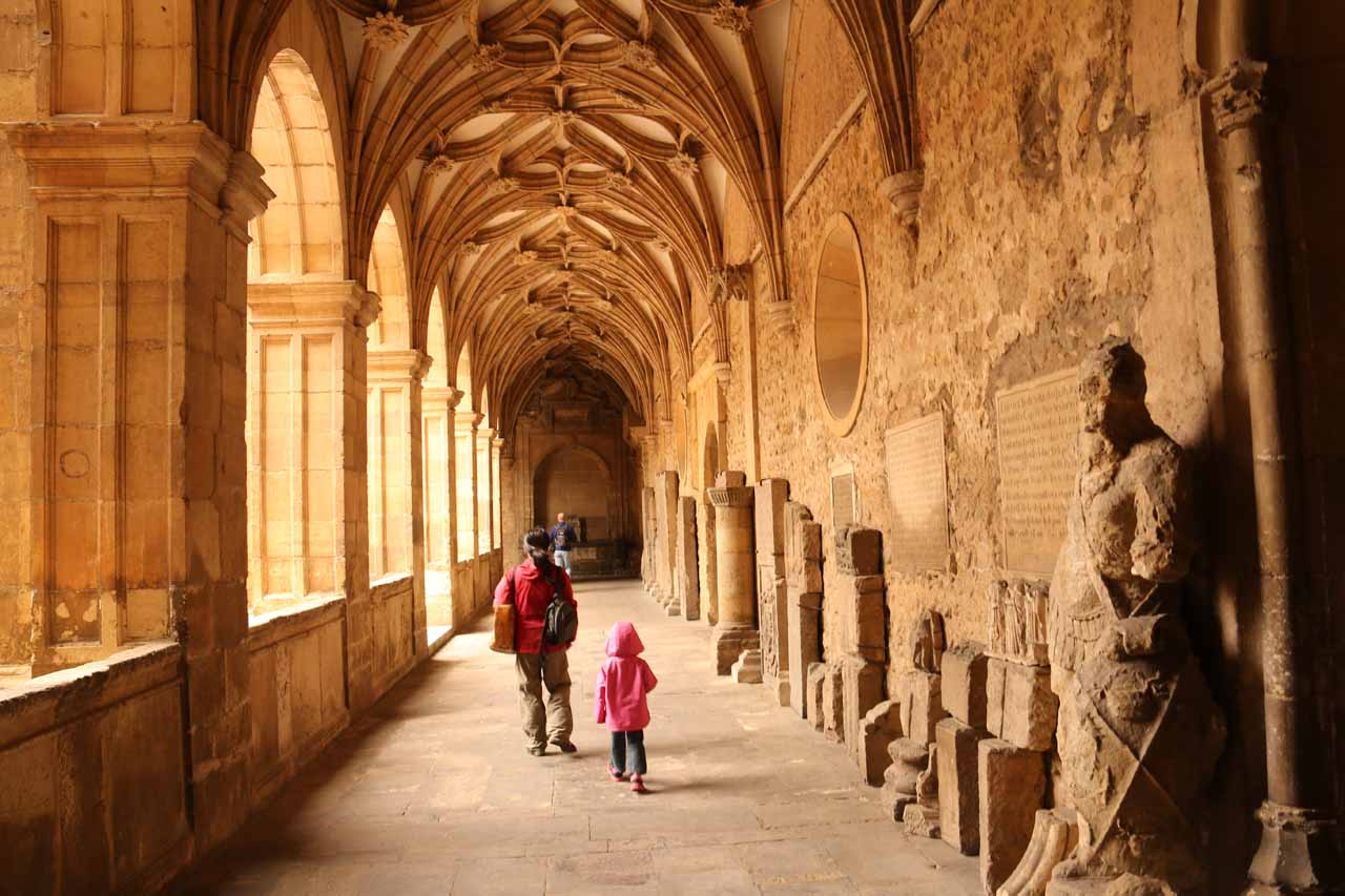 Julie and Tahia walking by some statues flanking the courtyard in the Basilica de San Isidro in Leon