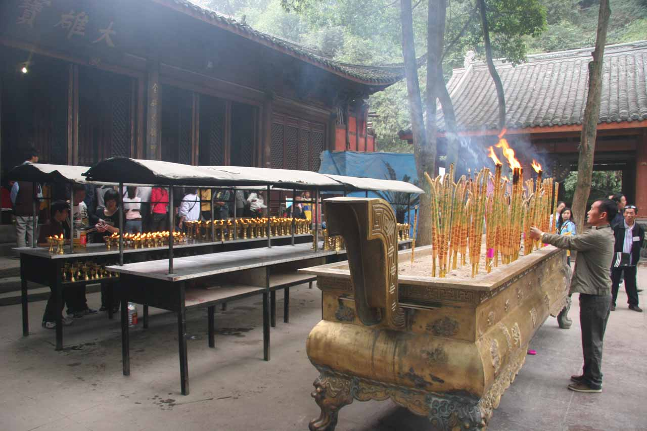 Burning incense near some shrines at the Grand Buddha site