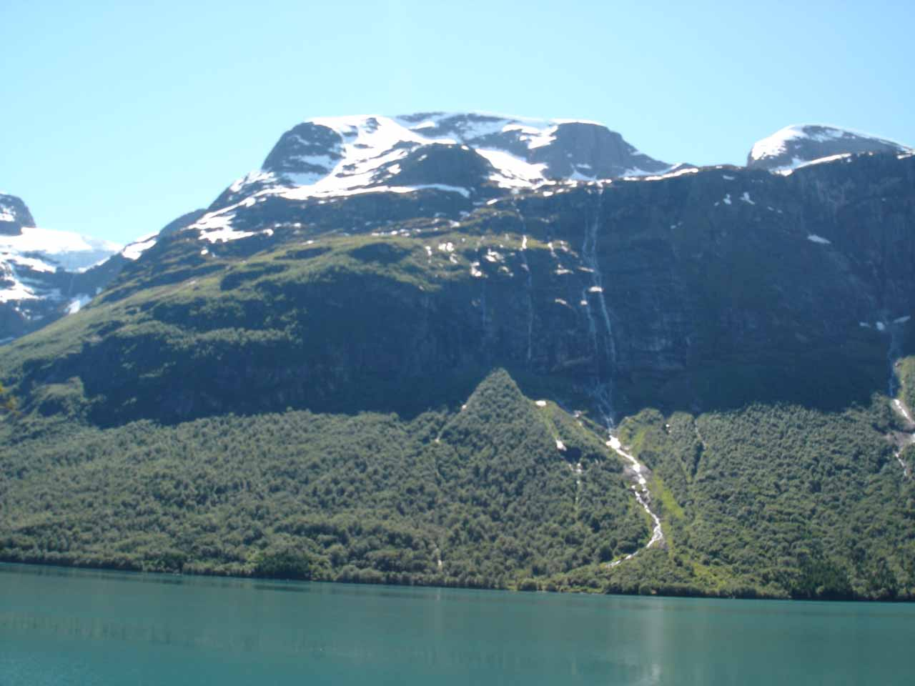 Looking across the lake Lovatnet towards other tall and stringy waterfalls spilling into Lodalen Valley