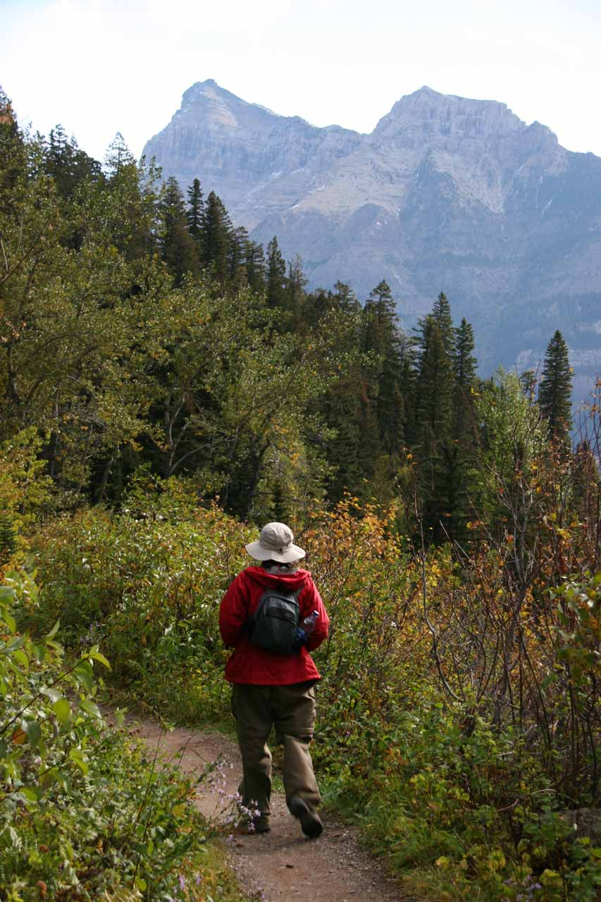 Julie heading back towards the trailhead with scenic mountains ahead of her