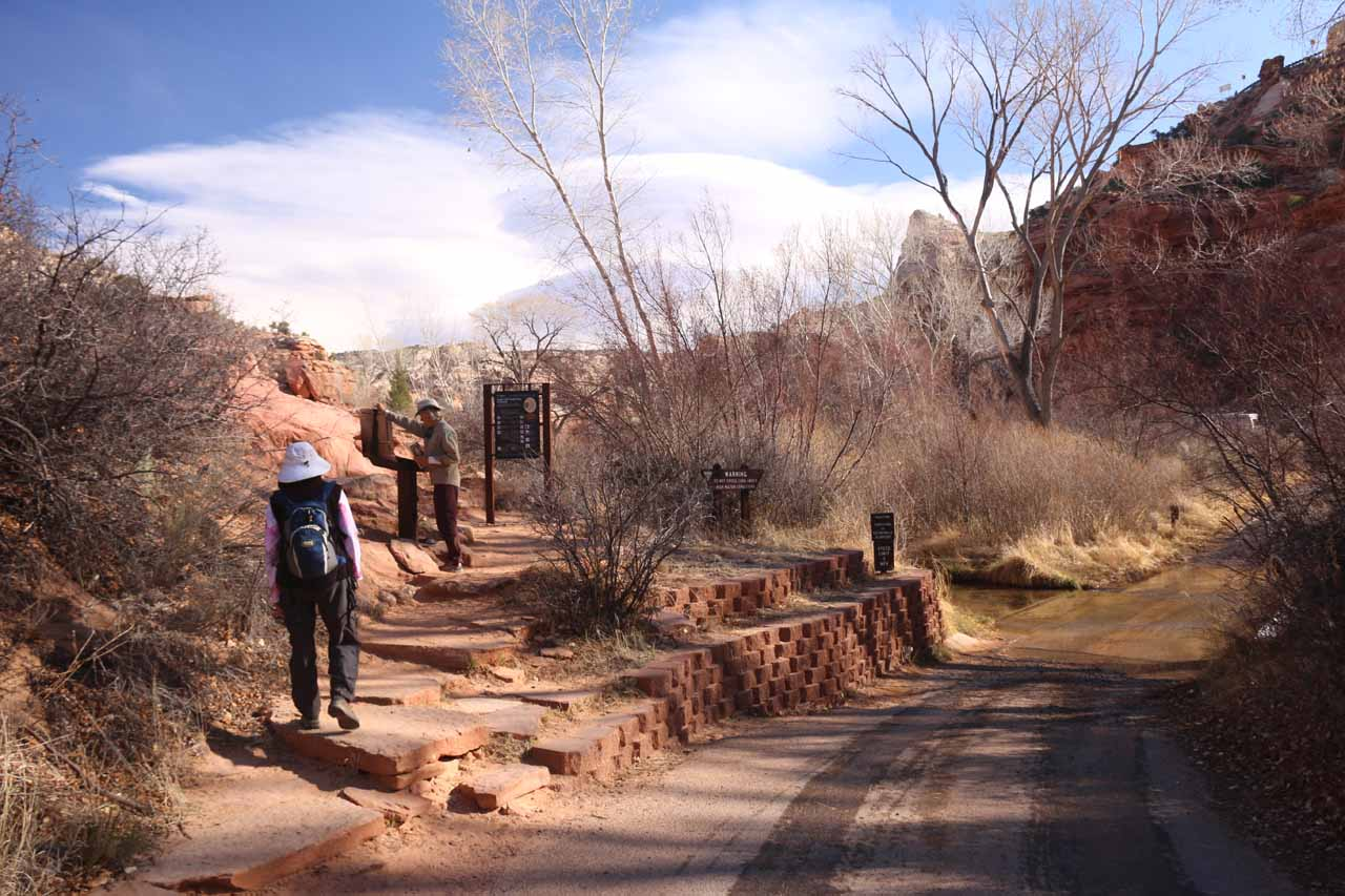 A ranger tending to the trailhead register at the official start to the hike. Note the concrete ford over Calf Creek to the right