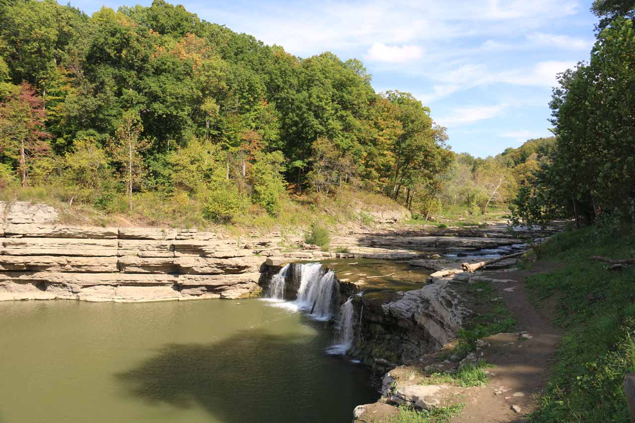 Broad view of the Lower Cataract Falls, the trail getting closer to its brink, and its surrounding limestone gorge walls