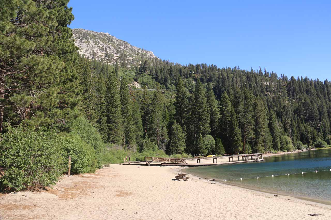 Looking along a beach on Emerald Bay revealing a little swim area as well as some picnic tables