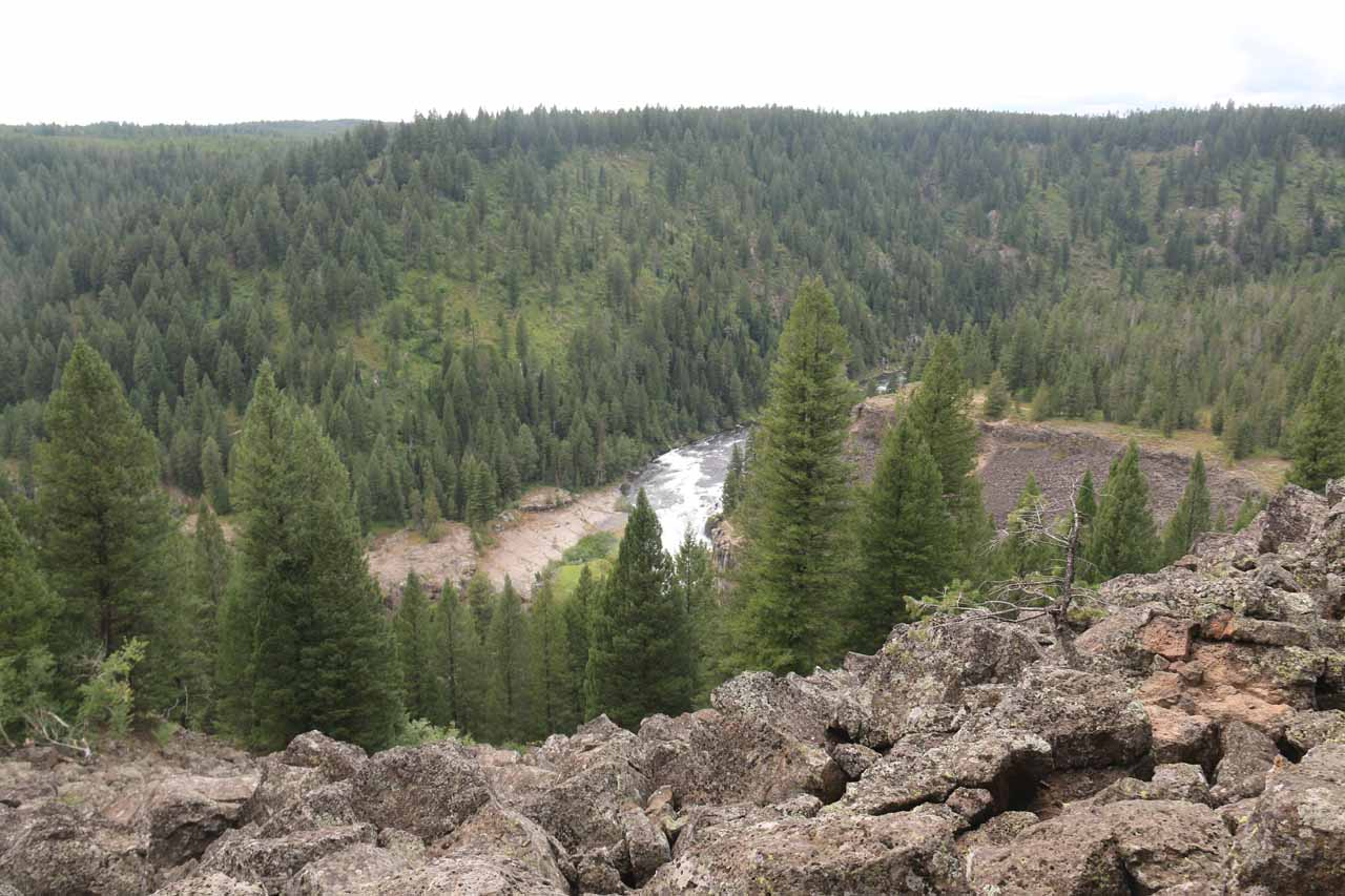 Volcanic boulders fronting this context of the Lower Mesa Falls gushing way in the distance
