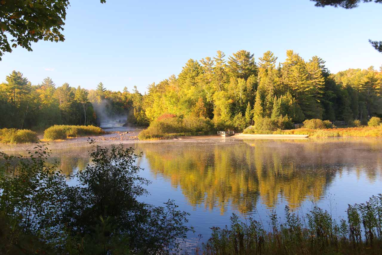 Broad view across a calm and wide part of the Tahquamenon River reflecting trees as well as providing a distant view of the left side of the Lower Tahquamenon Falls. We still had some morning fog around the waterfall to contend with though