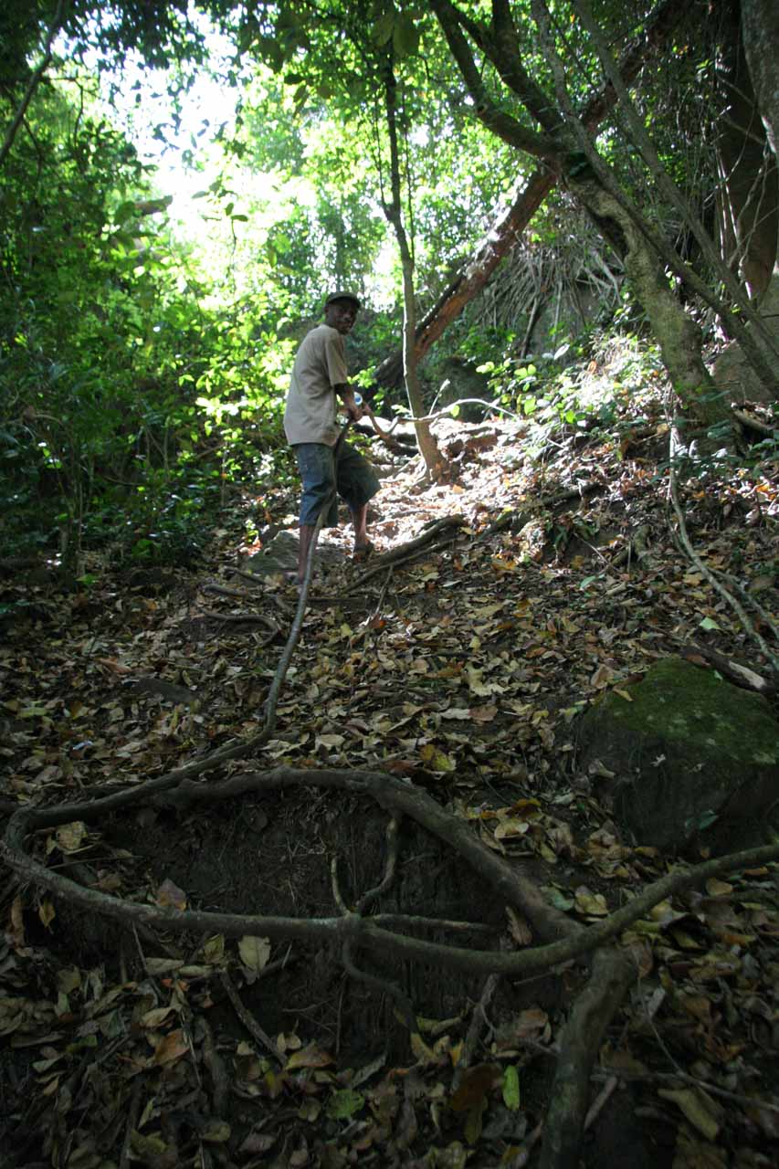 Using the rope vine to descend to the base of the falls