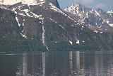 Lyngen_Alps_286_07072019 - Zoomed in look at Vakkasjohka waterfall with a lone fishing boat floating on the Lyngen Channel for scale