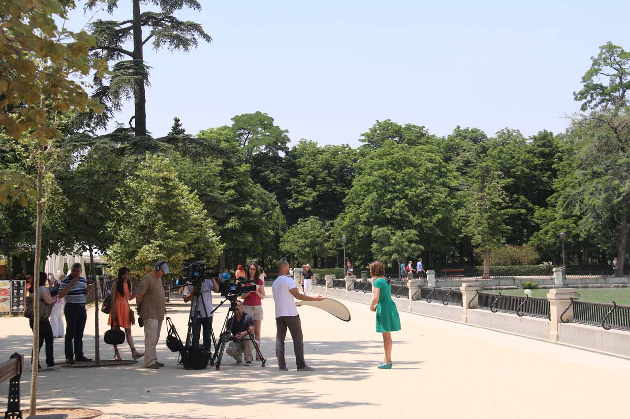Looking towards a film crew recording some lady dressed in green talking to the camera
