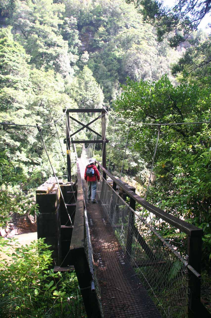 Julie about to cross over a swinging bridge near Mangatini Falls