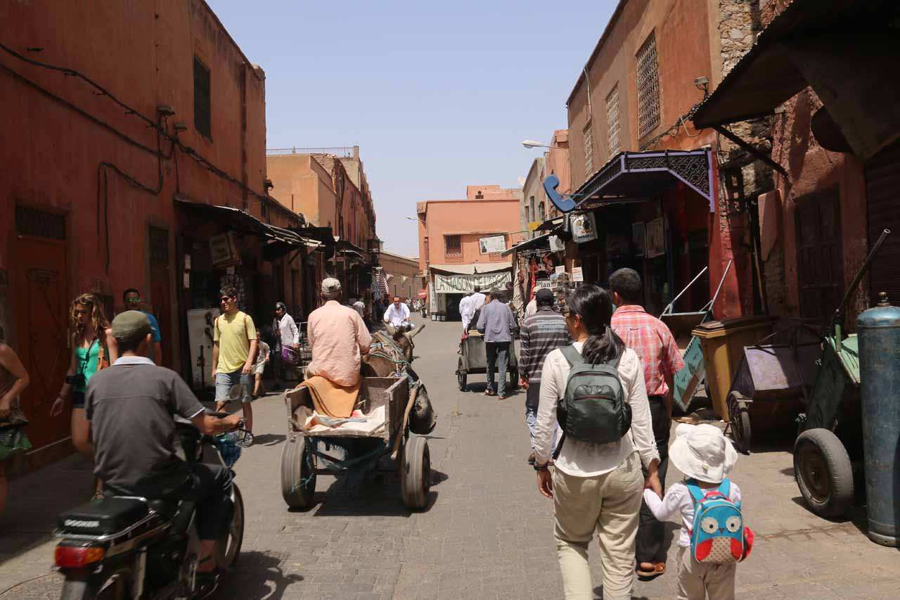 Following the porter and employee towards our riad while being passed by motorized scooters in the medina of Marrakech