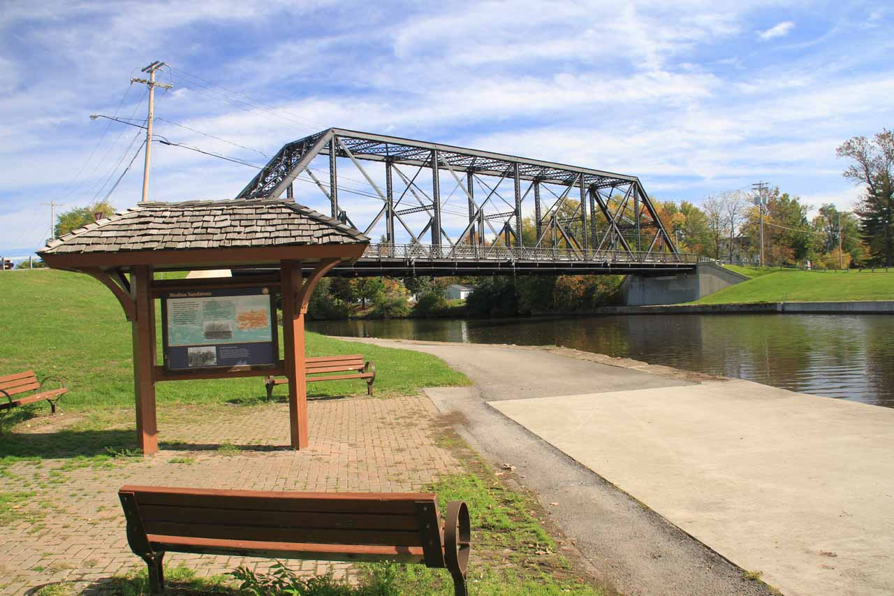 The interpretive signs surrounded by benches near the steel bridge spanning the Erie Canal