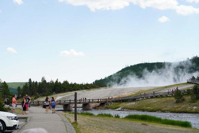 Midway_Geyser_Basin_008_08032020 - Context of the bridge and boardwalk crossing the Firehole River and ascending into the Midway Geyser Basin as seen from the very busy parking lot