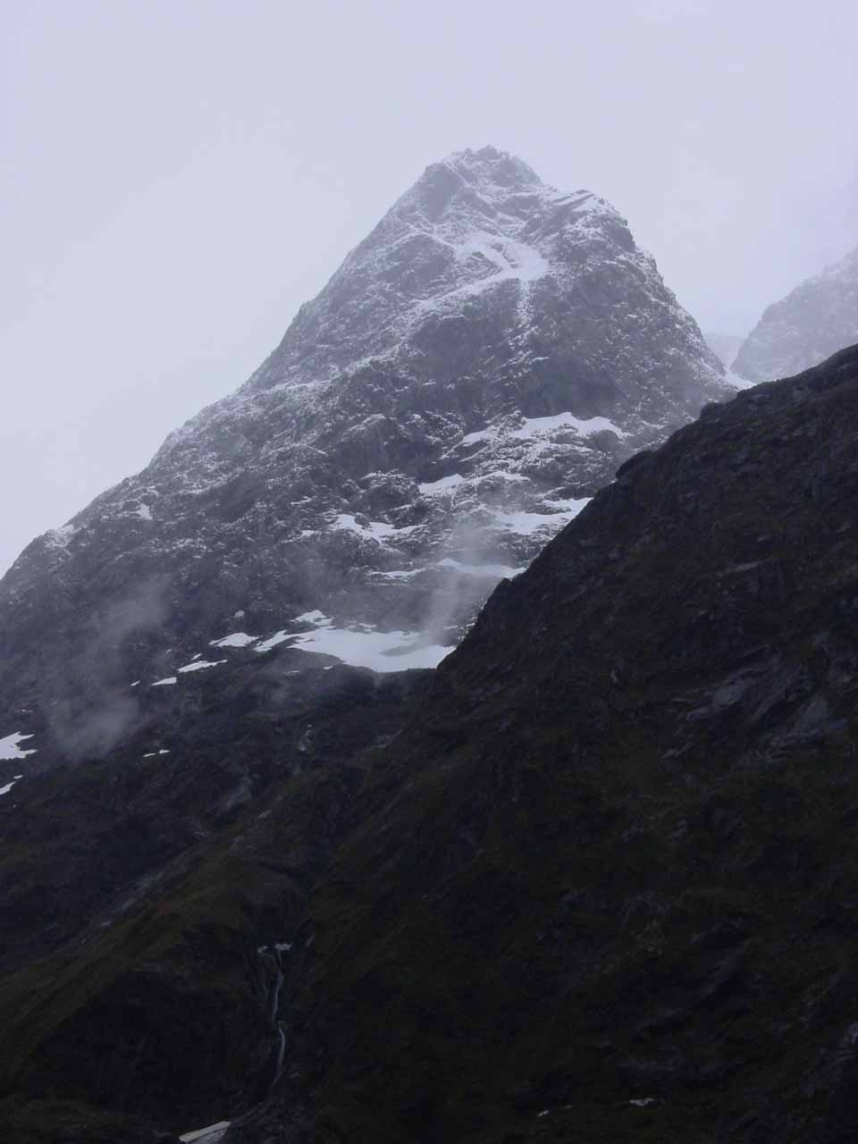 Looking up towards a tall mountain somewhere between Homer Tunnel and Christie Falls