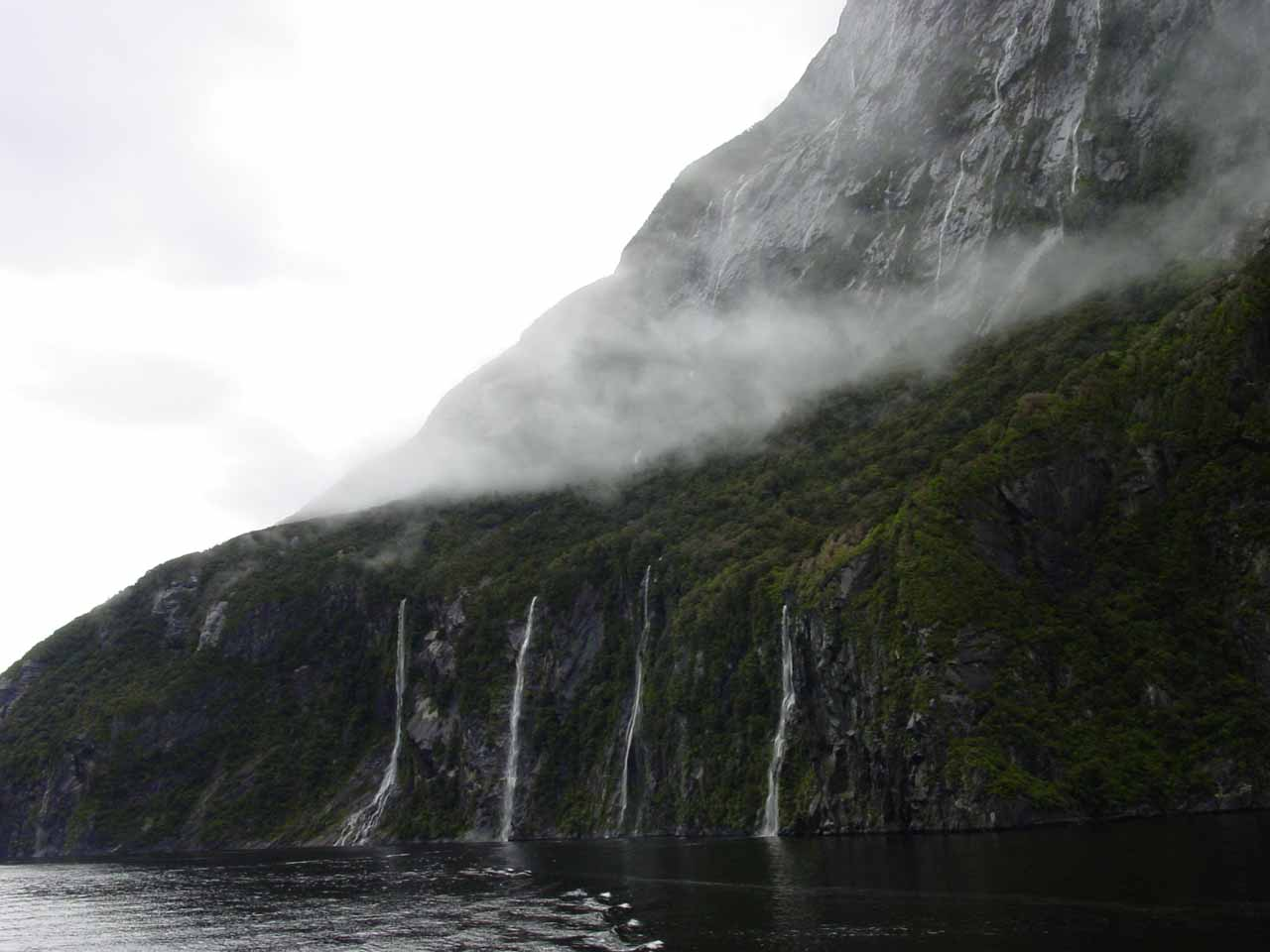 Looking back at a foursome of parallel waterfalls beneath Mitre Peak