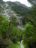 Milford_Track_day2_083_11272004 - Context of Julie continuing up ahead on the Milford Track with some more ephemeral waterfalls tumbling in front of her