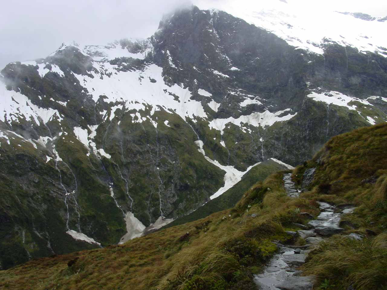 Descending into the Arthur Valley side of the Milford Track with many waterfalls and some snow coming down