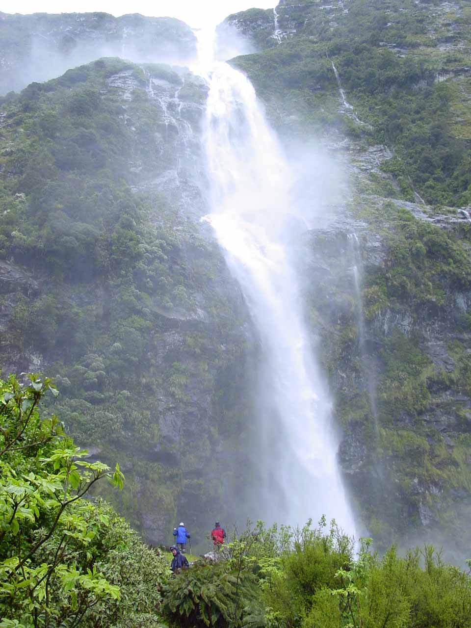 Some people being dwarfed by Sutherland Falls even with the forced perspective