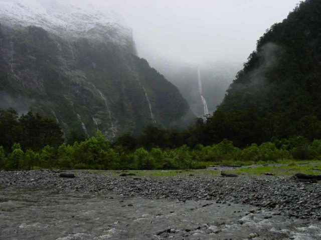 Milford_Track_day4_007_11292004 - Last look back at Sutherland Falls flanked by other waterfalls and newly-dumped snow under some low clouds as seen from the Milford Track at the start of day 4