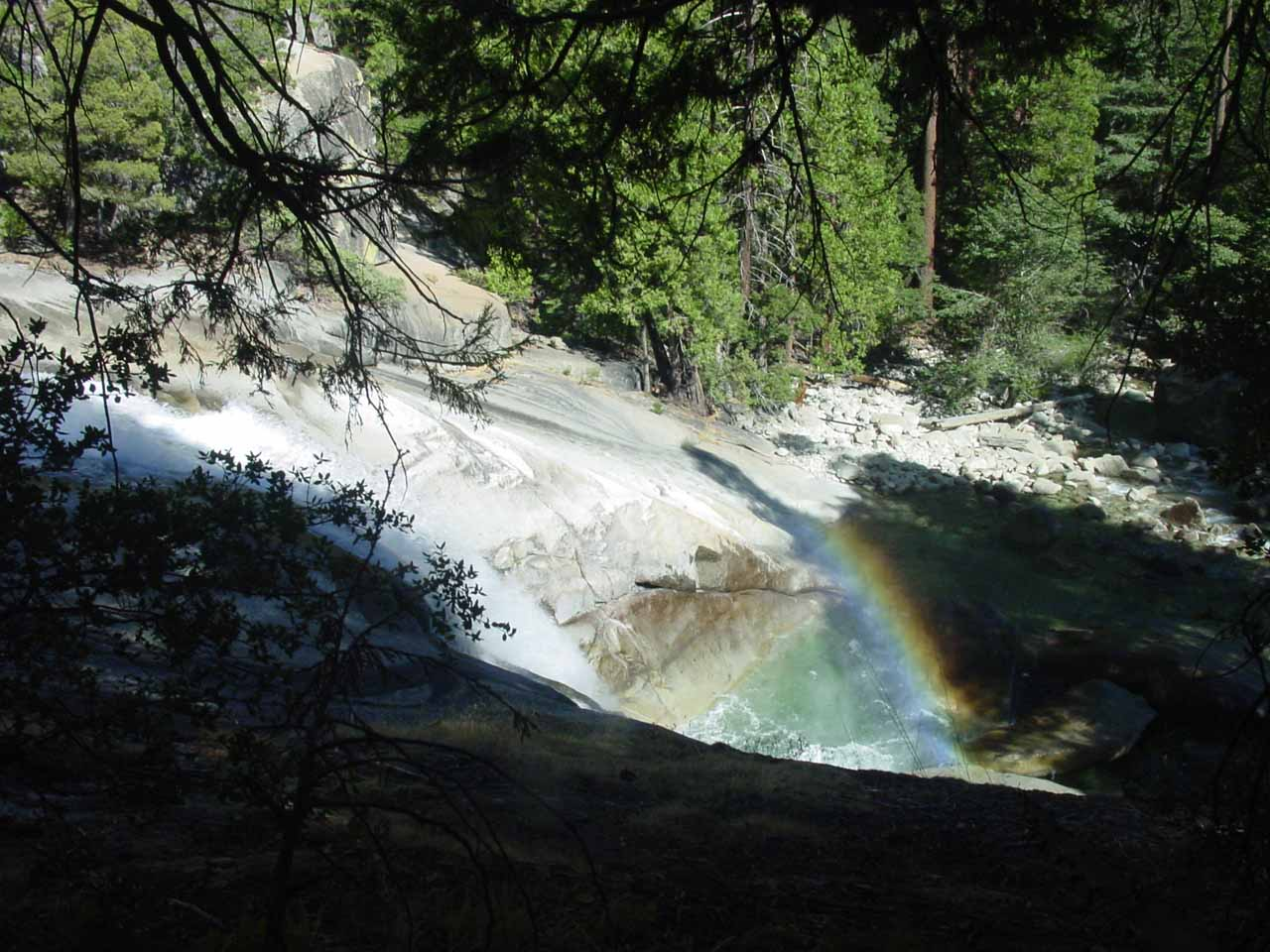 Looking down over the top of Mist Falls towards a rainbow and its pool