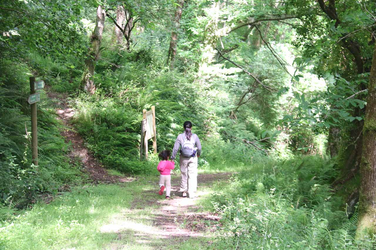 Julie and Tahia going past a sign by a trail junction on the way back to the car