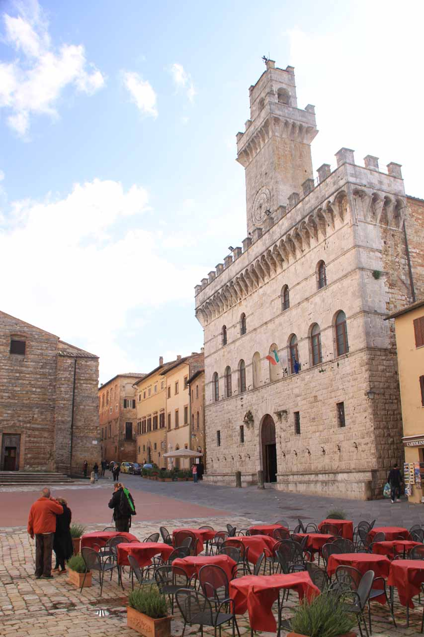 Some restaurant tables fronting the church and clock tower at the piazza in Montepulciano