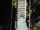 Montezuma_Falls_033_jx_11272006 - The suspension bridge was barely wide enough to accommodate the width of both of Julie's feet. Note how far down Avon Creek or Montezuma Creek was below the bridge