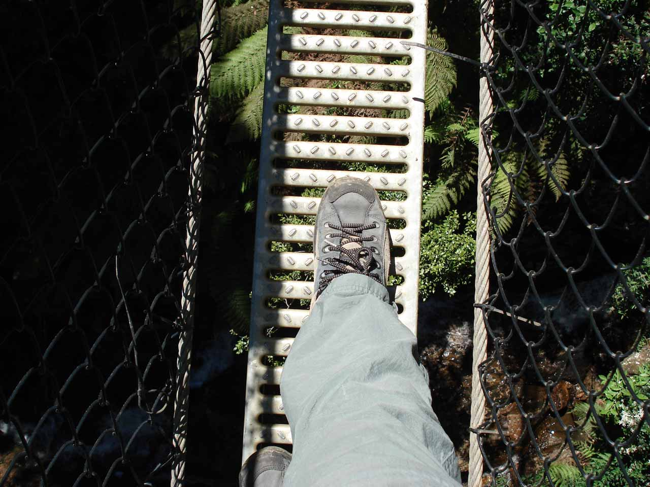 The suspension bridge was barely wide enough to accommodate the width of both of Julie's feet. Note how far down Avon Creek or Montezuma Creek was below the bridge