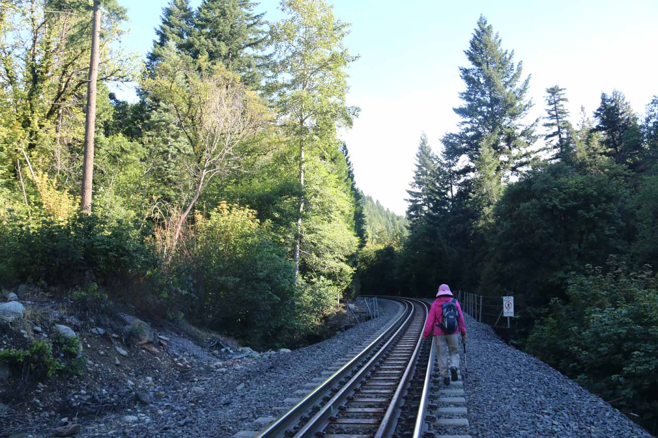 Mom hiking on the concrete railroad ties along one of the more narrower parts of the railroad tracks