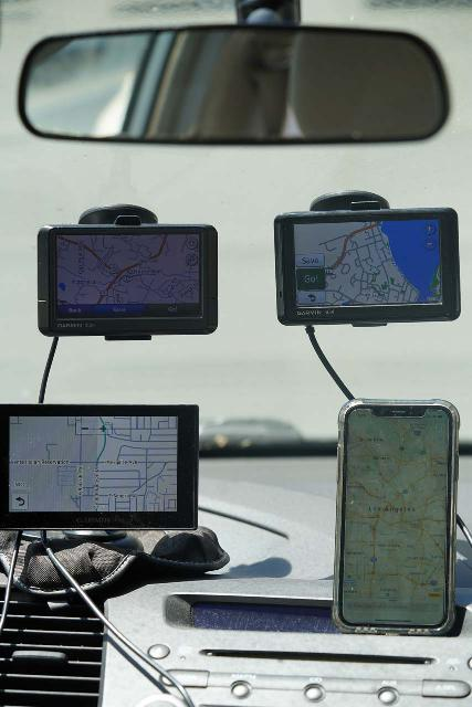 A medley of portable auto GPS navigation system devices. 2 are mounted on the windshield, 1 is mounted on the dash, and the iPhone (lower right) is free-standing on the dash