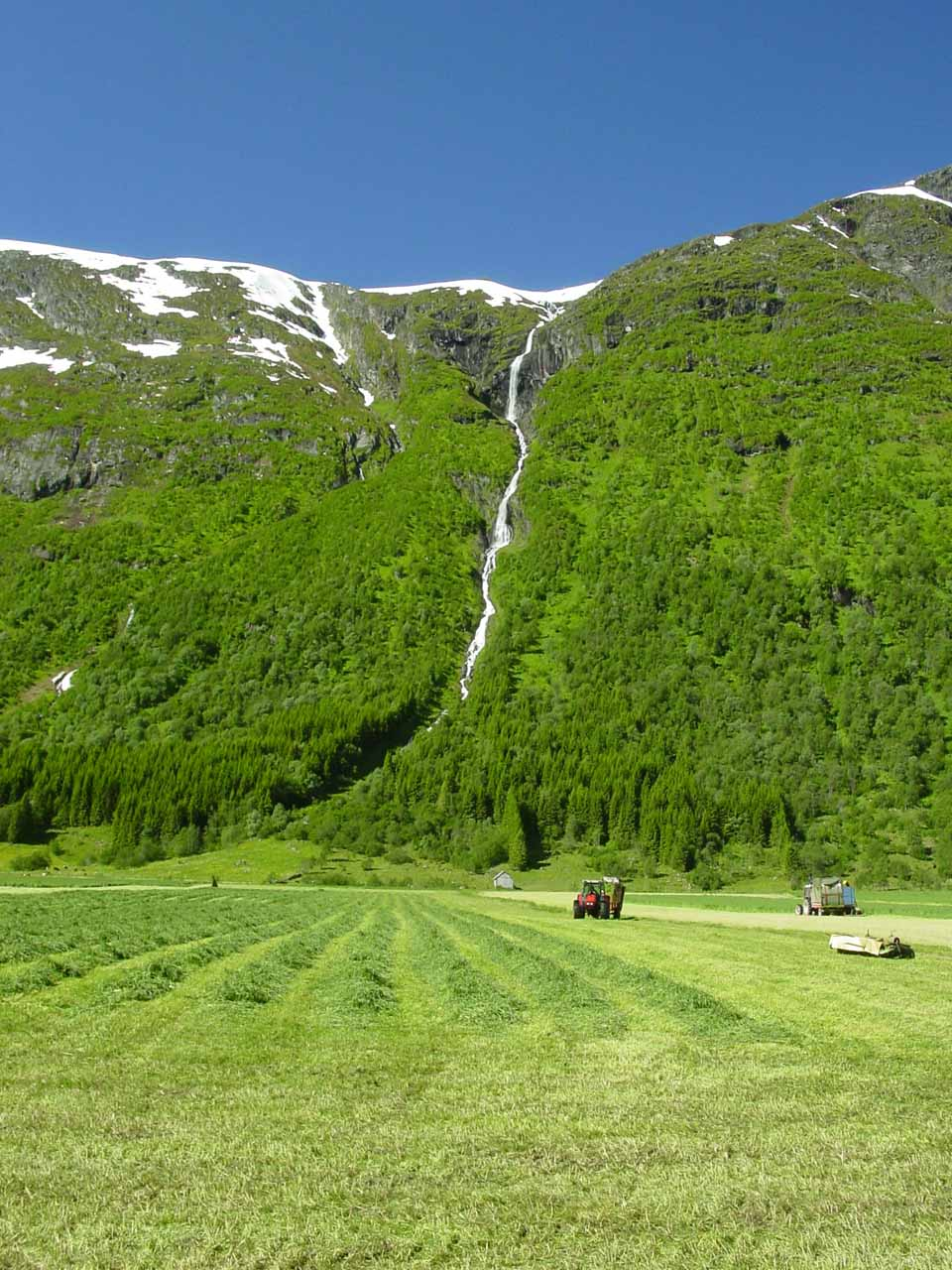 More direct look at Nonfossen and the farm field that a worker was tending to in the foreground