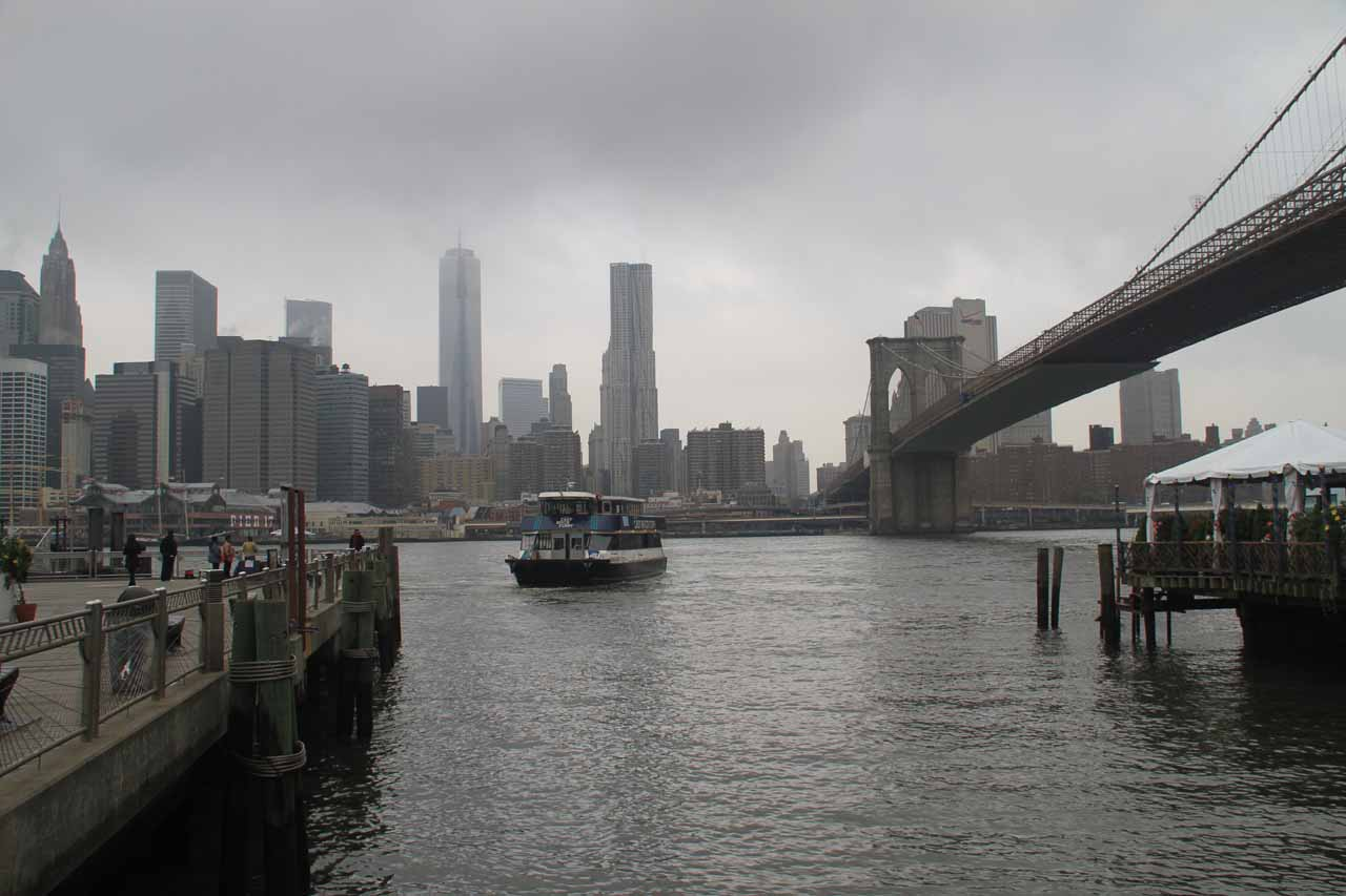 The New York skyline under overcast skies seen from near the Brooklyn Bridge