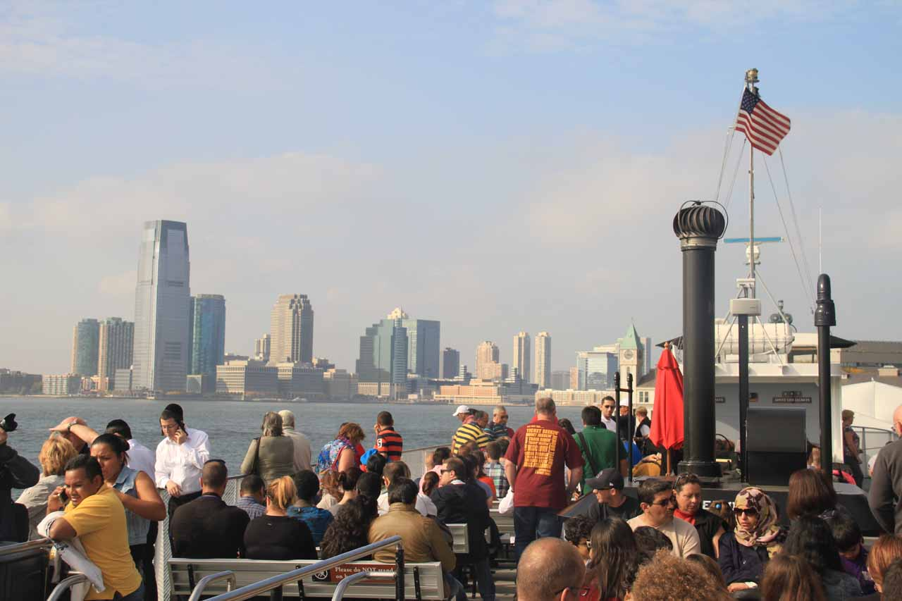 On the crowded upper deck of the boat to the Statue of Liberty