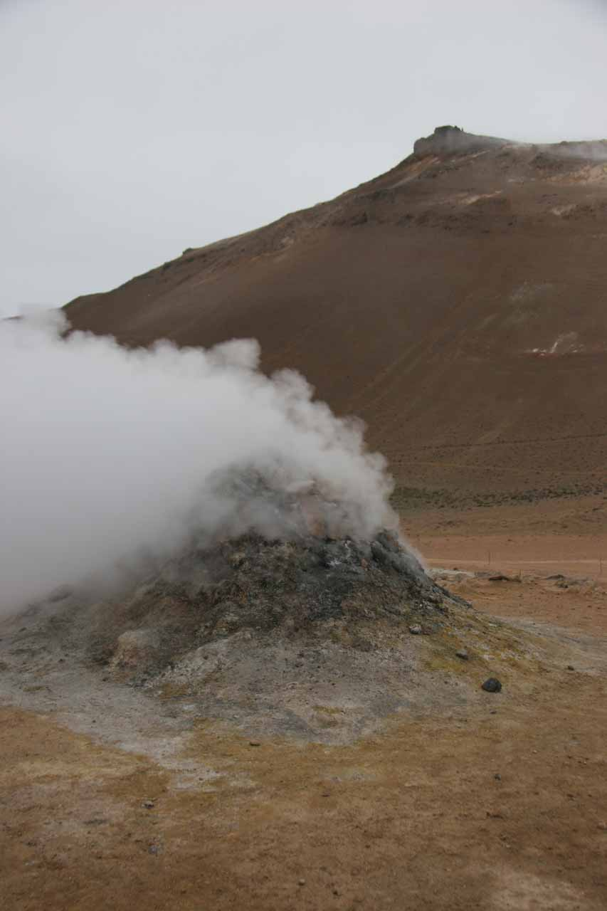 Another look at the hissing steam vent cone with some barren hills in the background