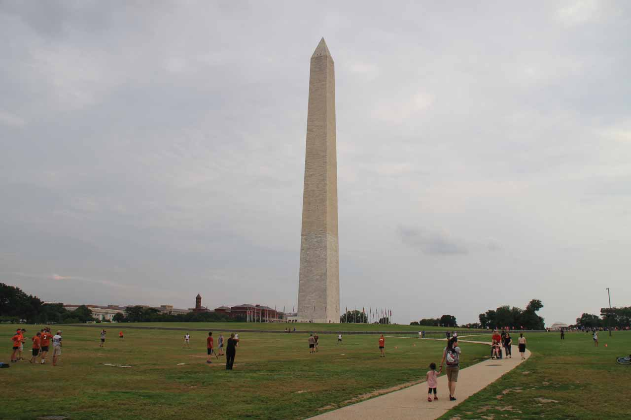 Julie and Tahia on the walkway leading closer to the Washington Monument with rec league softballers on the lawn
