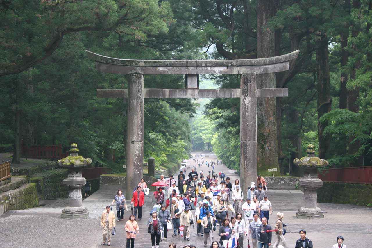 Large crowd walking beneath a large Torii at the Toshugu Shrine
