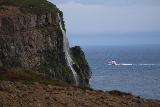 Ocean_Waterfall_telephoto_021_08142021 - Context of the Migandifoss Waterfall with a boat passing by it further in the distance