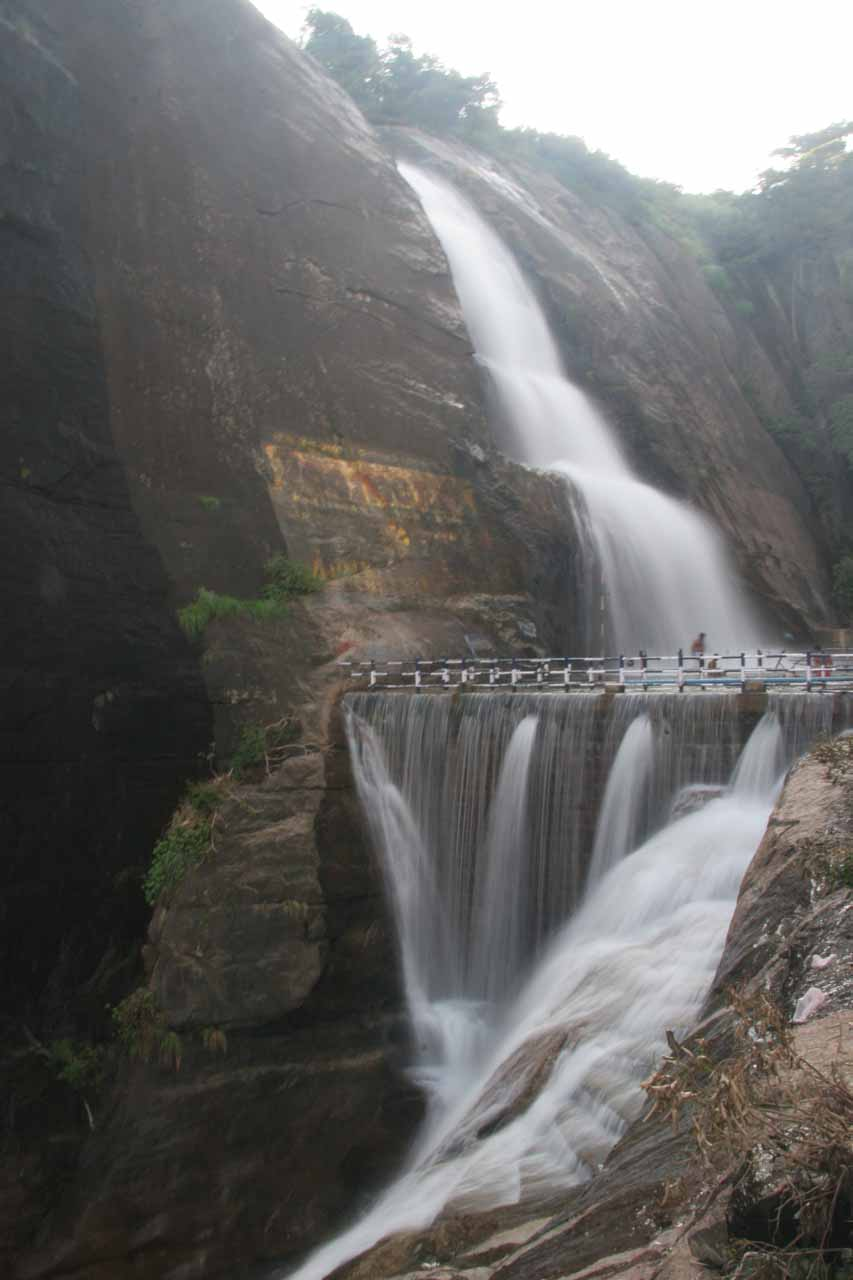 The full height of Old Courtallam Falls showing the stairstepping upper tiers followed by the twisting man-modified lower tiers