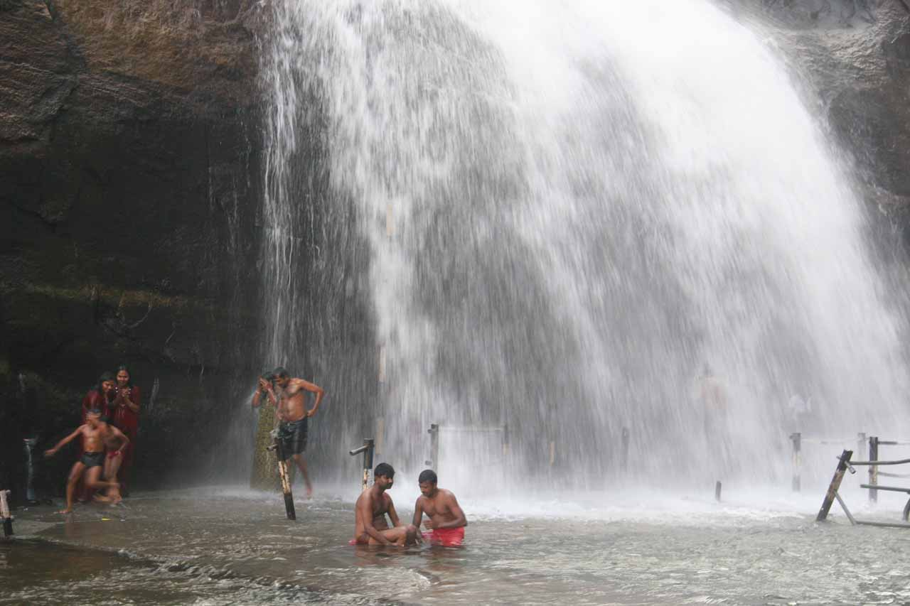 People bathing beneath the Old Courtallam Falls