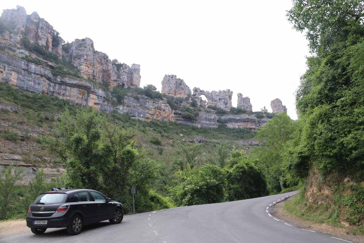 Looking towards cliff formations and a natural arch above a small car park area at Orbaneja del Castillo