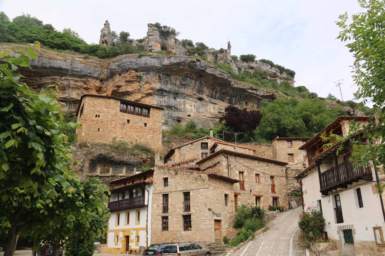Looking up at a steep road climbing even higher above Orbaneja del Castillo