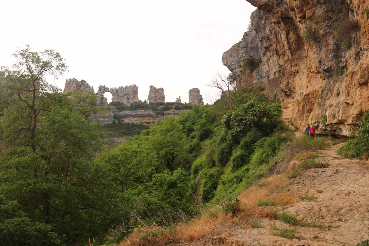 Looking away from a rugged alcove towards the cliff formations and natural arch across Orbaneja del Castillo