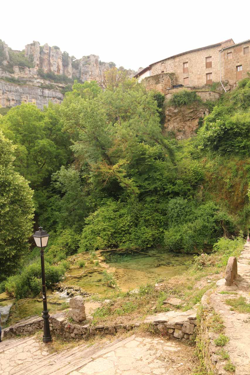 Looking across the stream responsible for the waterfall towards other buildings of Orbaneja del Castillo