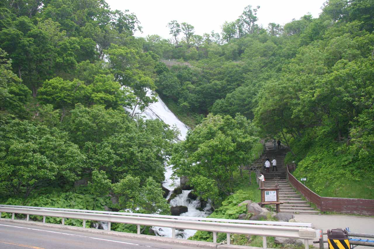 More contextual view of the Oshinkoshin Waterfall and the stairs fronting it from across the highway